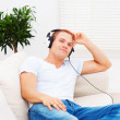 Smart young man listening to music while relaxing at home - Lizenzfreies Foto