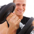 Young guy exercising with dumbbell, focus on the dumbbell - Stock Photo