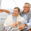 Mature couple on a sea voyage, man pointing away - Stock Photo
