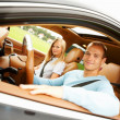 Happy young couple seated in their new car - Stockfoto