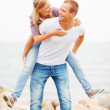 Happy young man piggybacking his girlfriend, outdoors - Stock Photo