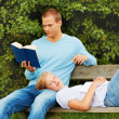 Young man reading a book in the park while girlfriend sleeping o - 图库照片
