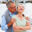 Senior husband and wife laughing while on a sailboat voyage - Foto de Stock