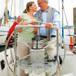 Romantic mature couple on a sea voyage, steering the boat - Stock Photo