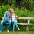 Young couple seated on a bench in the garden - Stock Photo