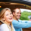 Happy young couple seated in their new car, focus on female - Stock Photo