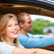 Happy young female enjoying a drive with boyfriend - Stock Photo