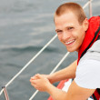 Happy young guy wearing a life jacket in a sail boat at sea - Stock Photo