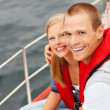 Royalty-Free Stock Photo: Cute young couple wearing life jacket smiling during a sea voyag