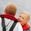 Royalty-Free Stock Photo: Pretty young woman in a life jacket with her boyfriend on a sea