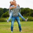 Happy young man piggybacking his girlfriend, at the park - Foto Stock