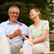 Royalty-Free Stock Photo: Happy senior couple holding a flower together while at the park