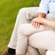 Royalty-Free Stock Photo: Mid section of a couple sitting on a bench at a park