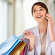 Royalty-Free Stock Photo: Young woman enjoying a conversation on the phone while shopping