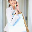 Elegant woman speaking on the cellphone while at shopping - Stockfoto
