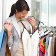 Happy woman selecting clothes whole at the mall - Stock Photo