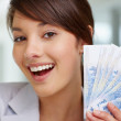 Closeup of a woman with currency notes , fan of notes - Stock Photo