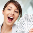 Pretty young woman holding currency notes and smiling - Foto Stock
