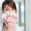Female with a fan of currency notes over her face - Stock Photo