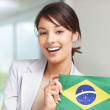 Happy young female with a Brazilian flag - Stock Photo
