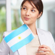 Pretty young woman with an Argentinian flag - Stock Photo