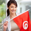 Cute young woman holding a Tunisian flag - Stock Photo