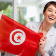 Pretty young female holding a Tunisian flag - Stock Photo