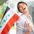 Royalty-Free Stock Photo: Cute woman laughing while holding an Iraqi flag , looking away