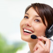 Female call centre employee speaking on  headset - Stock Photo