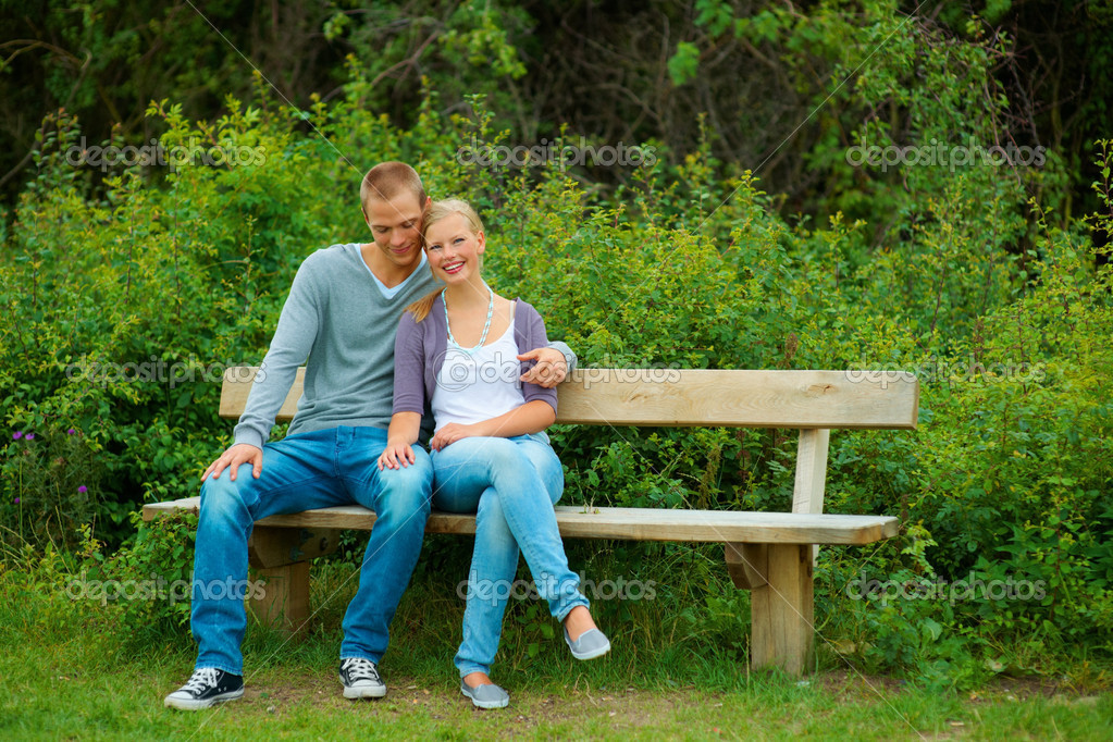 Happy young couple sitting together on a bench at a park — Stock Photo #3407266