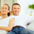 Happy mature couple sitting together on a couch - Stockfoto