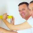 Happy handyman using a level on a wall being assisted by a woman - Stock Photo