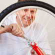 Royalty-Free Stock Photo: Happy man repairing a bicycle tyre