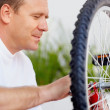 Closeup of a man repairing a bicycle tyre - Stock Photo