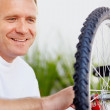 Royalty-Free Stock Photo: Closeup of a happy man repairing a bicycle tyre