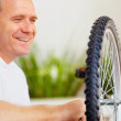 Royalty-Free Stock Photo: Happy man fixing a bicycle tyre