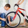 Man checking the tyre pressure of wife&#039;s new bicycle - Stockfoto