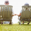 Royalty-Free Stock Photo: Rear view of a peaceful senior couple sitting on chairs outdoors