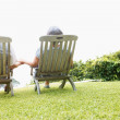 Royalty-Free Stock Photo: Rear view of a romantic senior couple on chairs outdoors