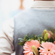 Royalty-Free Stock Photo: Man hiding flowers before a woman