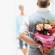 Senior man hiding flowers before a woman - Stock Photo