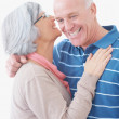 Senior woman whispering something into her husband's ear - Stock Photo