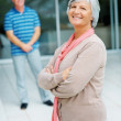 Royalty-Free Stock Photo: Confident old woman with her husband standing in the background