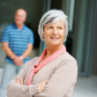 Royalty-Free Stock Photo: Thoughtful old woman with her husband standing in background