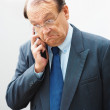 Bad News - Senior business man using a mobile phone - Stock Photo