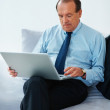 Relaxed senior business man using laptop at his home - Stock Photo