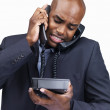 Businessman with two telephones at the same time - Stock Photo