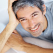 Closeup portrait of smiling man lying on sofa - Stock Photo
