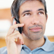 Casual businessman speaking on cellphone looking away in thought - Foto Stock