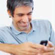 Casual man enjoying while typing text message - Stok fotoraf